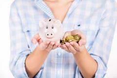 Ręki trzyma prosiątko monet i banka jako symbol pieniądze oszczędzanie i Fotografia Royalty Free