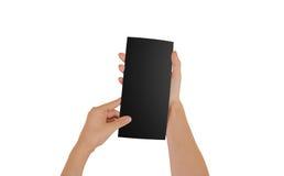 Ręki trzyma pustą czarną broszurki broszurę w ręce ulotka Fotografia Stock