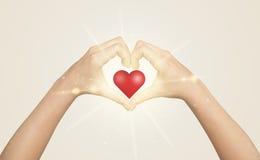 Ręki tworzy formę z olśniewającym sercem Zdjęcia Stock