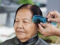 Ręki use grępla opatrunkowy włosy starsza kobieta Obrazy Stock