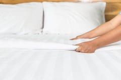 Ręki ustawiania biały łóżkowy prześcieradło w pokoju hotelowym zdjęcie stock