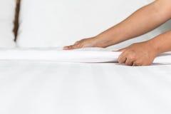 Ręki ustawiania biały łóżkowy prześcieradło w pokoju hotelowym Fotografia Stock