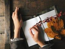 Ręki utrzymania notatnik z białymi czystymi prześcieradłami na drewno stole Jesień liście, grżą kolory, rocznik tekstura Copyspac Zdjęcie Royalty Free