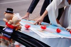 Ręki właśnie zamężni potomstwa dobierają się na mapie honeymoon zdjęcie stock