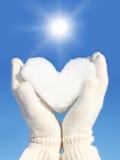 Ręki w białych rękawiczkach trzyma śnieżnego serce przeciw zdjęcie royalty free