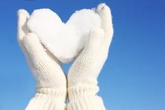 Ręki w białych rękawiczkach trzyma śnieżnego serce obrazy stock