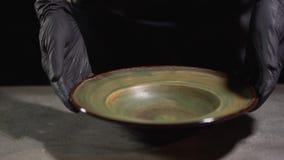 Ręki w czarnych karmowych rękawiczkach stawiają dużego pustego talerza na zgłaszają powierzchnię Karmowego przygotowania początki zdjęcie wideo