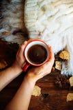 Ręki w czerwienie dziać rękawiczkach trzyma gorącą filiżankę kawy przeciw kolorowi żółtemu opuszczają tło Pojęcie czas, ciepło i  obraz royalty free