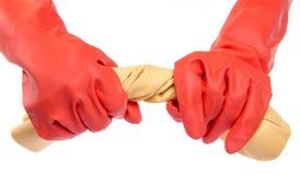 Ręki w czerwonych gumowych rękawiczkach wykręca płótno Obrazy Stock