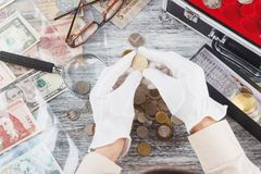 Ręki w rękawiczka chwyta poborcy złocistej monecie obrazy stock