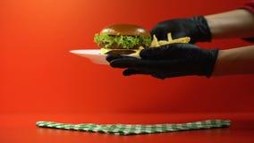 Ręki w rękawiczkach bierze oddalonego hamburger, prezentacja nowi kanapka przepisy zbiory
