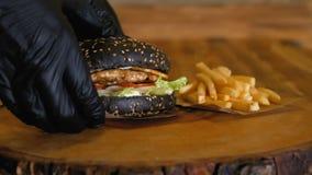 Ręki w rękawiczkach podnoszą w górę soczystego czarnego hamburgeru z cutlets i warzywami Niezdrowy fast food Francuscy dłoniaki p zbiory wideo