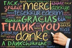 Ręki writing Dziękuje ciebie w wiele językach fotografia stock