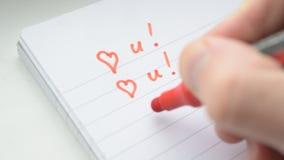 Ręki writing KOCHAM CIEBIE U z czerwonym markierem w notepad na białym tle zbiory