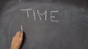 Ręki writing rozkład zajęć na czarnym chalkboard