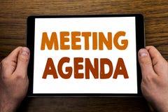 Ręki writing teksta podpisu spotkania agenda Biznesowy pojęcie dla Biznesowego rozkładu planu Pisać na pastylka laptopie, drewnia Zdjęcia Stock