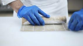 Ręki wykwalifikowany szef kuchni tworzy suszi z bambus matą zbiory