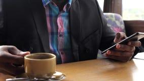 Ręki wyszukuje smartphone w kawiarni i pije kawę czarny biznesmen zdjęcie wideo