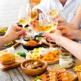 Ręki z czerwonym winem wznosi toast nad słuzyć stołem z jedzeniem Fotografia Stock