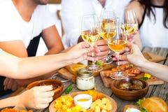 Ręki z czerwonym winem wznosi toast nad słuzyć stołem z jedzeniem Zdjęcia Stock