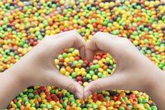 Ręki z kierowym symbolem i kolorowymi cukierkami zdjęcie stock