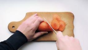 Ręki z nożem są tnącymi marchewkami Marchwiani plasterki na kucharstwo desce Dokładność i precyzja Odgórny widok zbiory