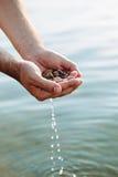 Ręki z otoczakami i wodą Zdjęcia Stock