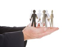 Ręki z papierowymi ludźmi reprezentuje jedność Fotografia Stock