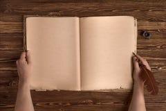 Ręki z rocznik dutki piórem, atramentem i starą książką na drewnianym tle, Fotografia Stock
