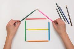 Ręki zakończenia budowy dom na kawałku papieru od kredek Obrazy Royalty Free