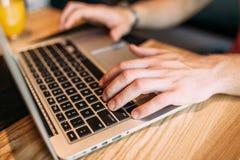 Ręki zamykają up palce pisać na maszynie na laptopie, mężczyzna w kawiarni obrazy royalty free