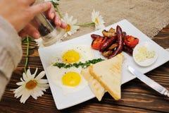 Ręki zbliżenia pieprzu czarny pieprz na rozdrapanych jajkach z bekonem i pieczarkami Obraz Stock