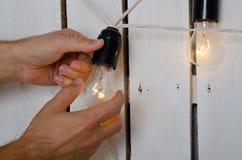 Ręki zmienia żarówkę Fotografia Stock