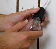 Ręki zmienia żarówkę w domu Obraz Royalty Free