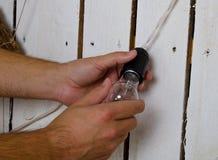 Ręki zmienia żarówkę w domu Obrazy Royalty Free