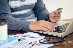 Rękojeści kredytowe karty z laptopami nabywali online Obraz Stock
