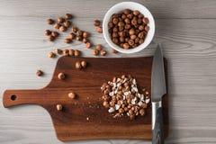 Rżnięci hazelnuts na drewnianej desce z nożem, składniki dla gotować, drewniany tło Obraz Stock