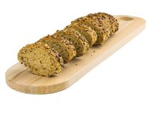 Rżnięci plasterki chleb od pszenicznej mąki z ziarnami na tnącej desce odizolowywającej na białym tle fotografia stock