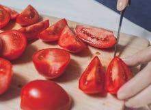 Rżnięci pomidory na tnącej desce z ręką Obraz Stock