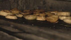 Rżnięta cebula gotuje na bbq grillu lub wśrodku piekarnika nad węglami w restauracji w slowmo smaży pokrojone cebule wewnątrz, ku zdjęcie wideo