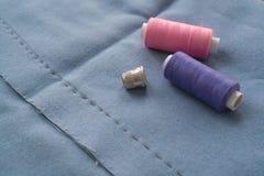 Rżnięta część spódnica z uszytą zakładką, naparstkiem i dwa cewami nić, Dwa cewy nici i krawczyny narz?dzie r??owe i purpurowe s? obraz stock