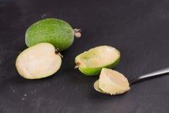 Rżnięta owoc dojrzały feijoa na ciemnym łupkowym tle Miąższowa owoc na korowatej łyżce zdjęcie royalty free