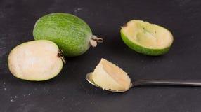 Rżnięta owoc dojrzały feijoa na ciemnym łupkowym tle Miąższowa owoc na korowatej łyżce obraz stock
