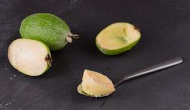 Rżnięta owoc dojrzały feijoa na ciemnym łupkowym tle Miąższowa owoc na korowatej łyżce obrazy royalty free