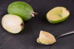 Rżnięta owoc dojrzały feijoa na ciemnym łupkowym tle Miąższowa owoc na korowatej łyżce obraz royalty free