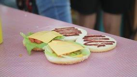 Rżnięte babeczki dla hamburgerów z ketchupem, serem i sałatą, zdjęcie wideo
