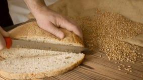 Rżnięty plasterek chleb na drewnianym stole w zwolnionym tempie, zamyka up zbiory