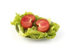 Rżnięty pomidor na zielonej sałatce opuszcza na zielonym ceramicznym naczyniu Obrazy Stock