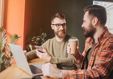Rżnięty widok faceci siedzi rozmowę i ma Na one dranking kawę podczas gdy inny wyjaśnia coś obrazy royalty free
