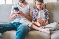Rżnięty widok obsiadanie na kanapie i patrzeć telefon mężczyzna i chłopiec w rękach Dziecko siedzi z nogami corssed obrazy stock